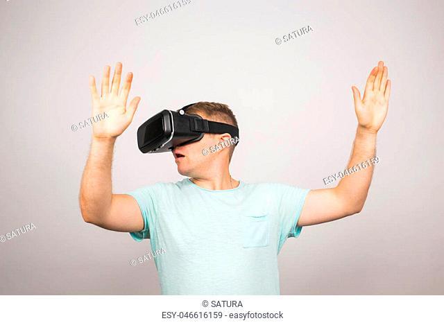 Man wearing virtual reality goggles. Studio shot, gray background