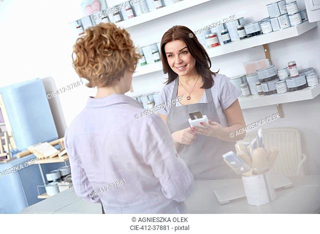 Female business owner using credit card reader, helping customer at counter in art paint shop