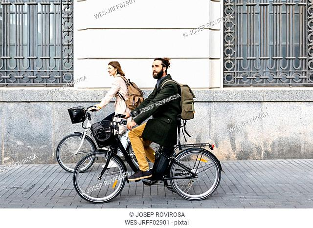 Couple riding e-bikes in the city passing a building