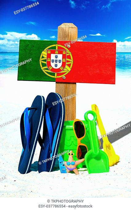 Wooden sigboard with the portugal flag, blue flip flops and colorful beach toys on the sunny beach