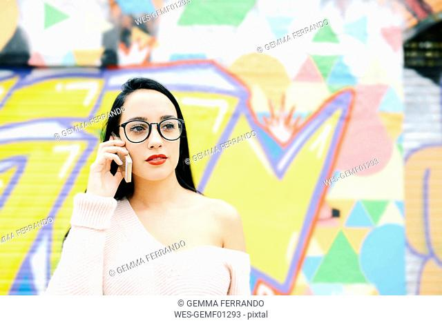 Portrait of woman on the phone in front of graffiti wall