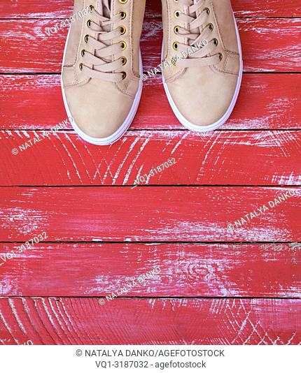 pink pair of female leather sneakers with laces on a red wooden background