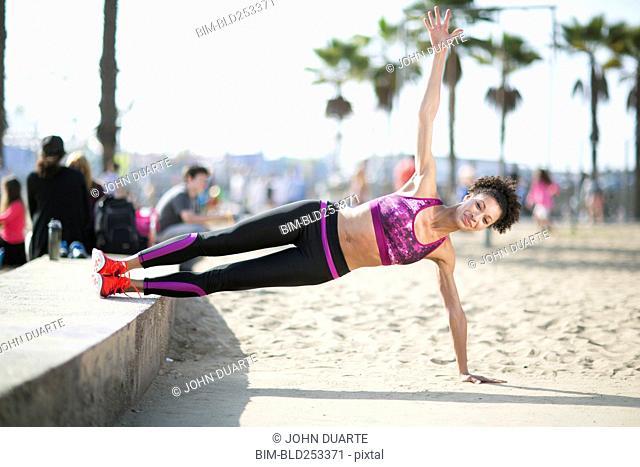 Mixed Race woman balancing on arm at beach