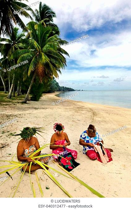 Portrait of Polynesian Pacific Island Tahitian mature females sewing Tivaivai and weaving a hat knees out of palm leaves on tropical beach in Aitutaki lagoon...
