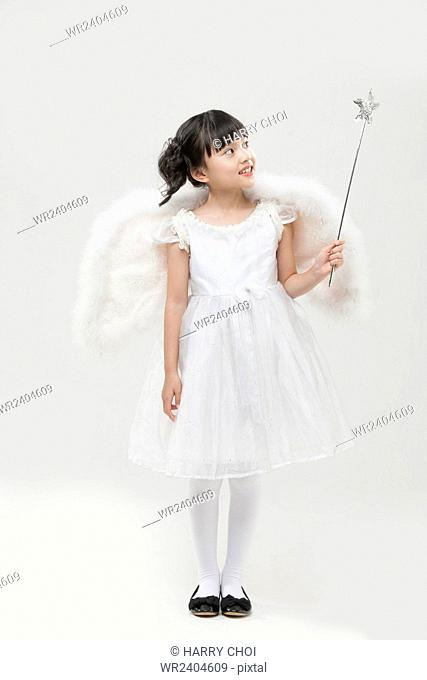 Smiling girl dressed like angel standing looking up