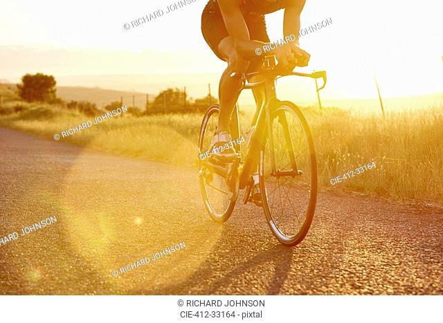 Male cyclist riding bike on sunny sunrise rural road