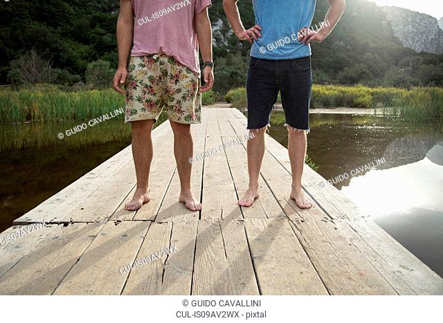 Waist down front view of young men on wooden pier, Cala Luna, Sardinia, Italy