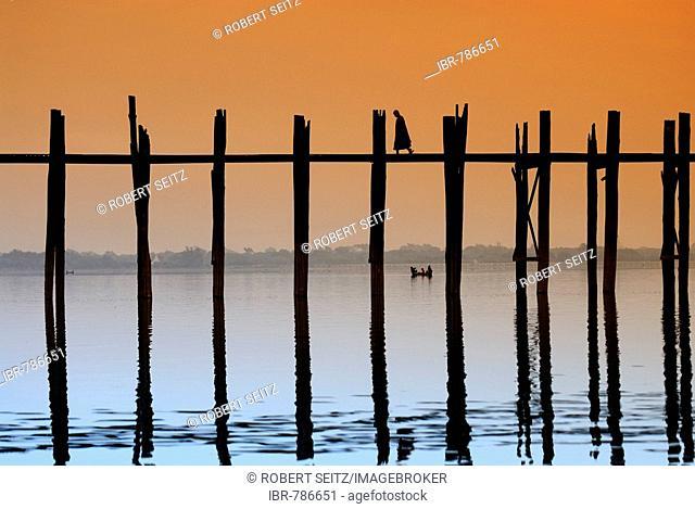 Monks crossing the U Bein Bridge at sunset, old wooden teak bridge, Mandalay, Myanmar, Southeast Asia