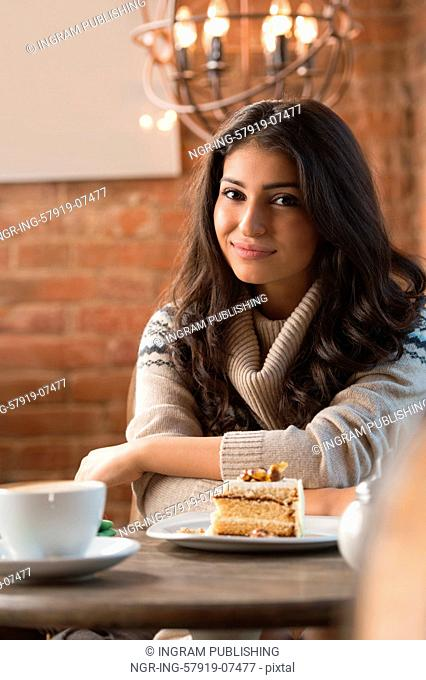 Young woman drinking coffee in a cafe indoors. Shallow depth of field