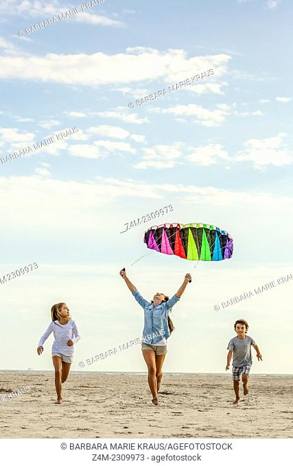 Two sisters and their brother fly a colorful kite on the beach. Coastal Georgia, USA