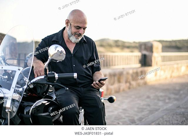 Spain, Jaen, mature man on his motorcycle with a sidecar looking at cell phone