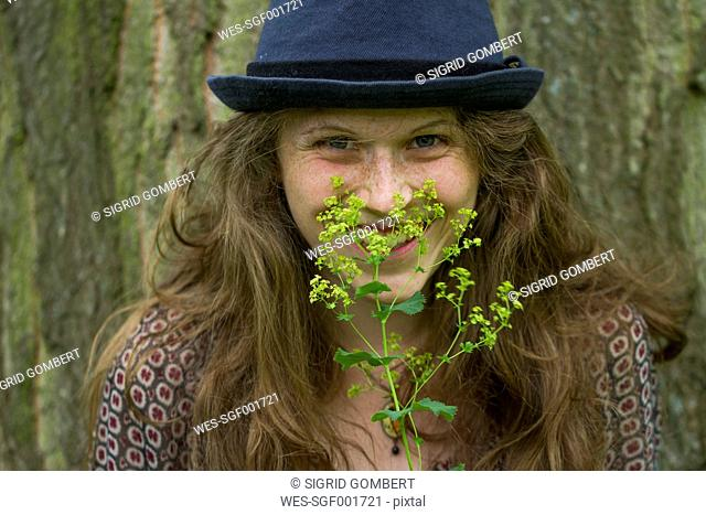 Portrait of smiling young woman with hat and blossoming twig