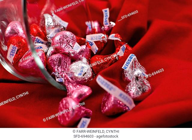 Pink, Red and Silver Chocolate Kisses Spilling From a Bowl