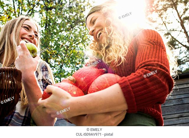 Two women holding homegrown produce, low angle