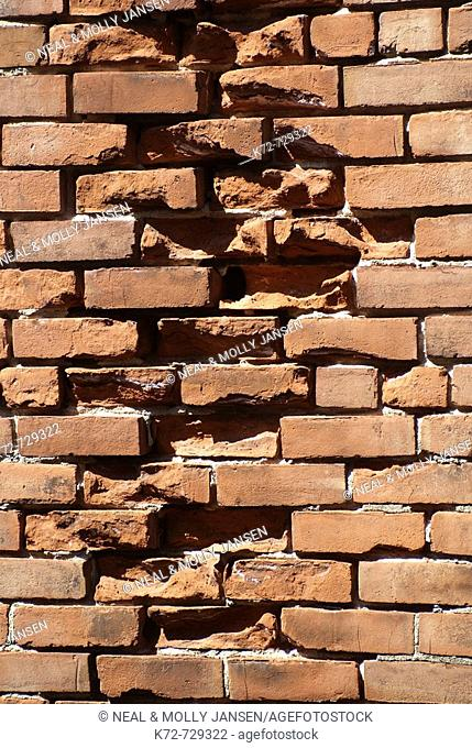 Broken bricks in a wall make it less stable