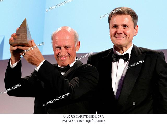 Businessman Willy Bogner (L) poses for a photo with the 'Goldene Sportpyramide' award next to Norbert Winkeljohann, spokesman of the PwC in Hotel Adlon in...