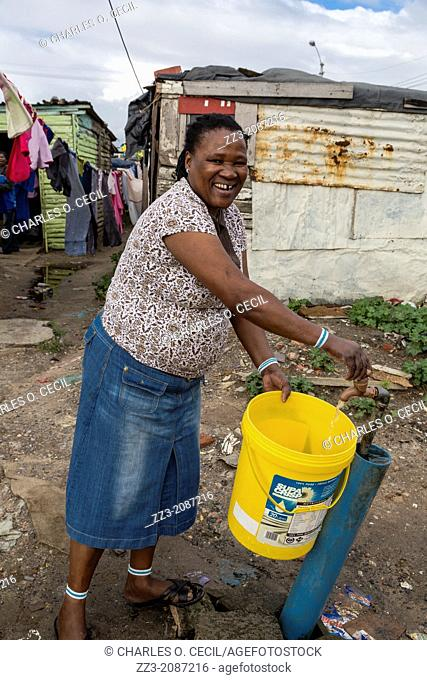 South Africa, Cape Town, Guguletu Township. Woman Getting Water at Communal Tap