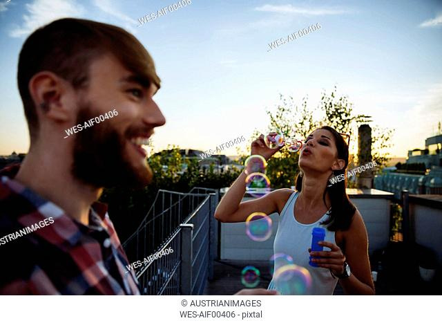 Young woman blowing soap bubbles on roof terrace