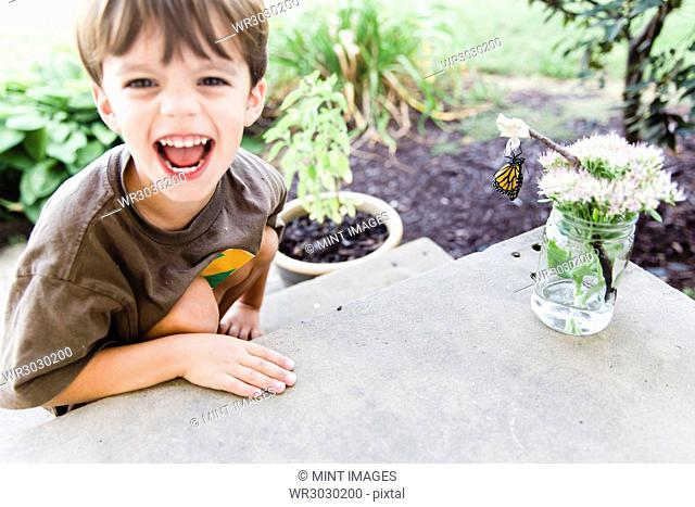 Boy, child next to a flower arrangement on a table with a butterfly hanging from a twig