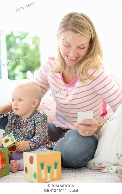 Mother playing with baby girl and checking cell phone