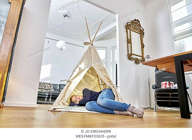 Woman lying in a teepee on the floor