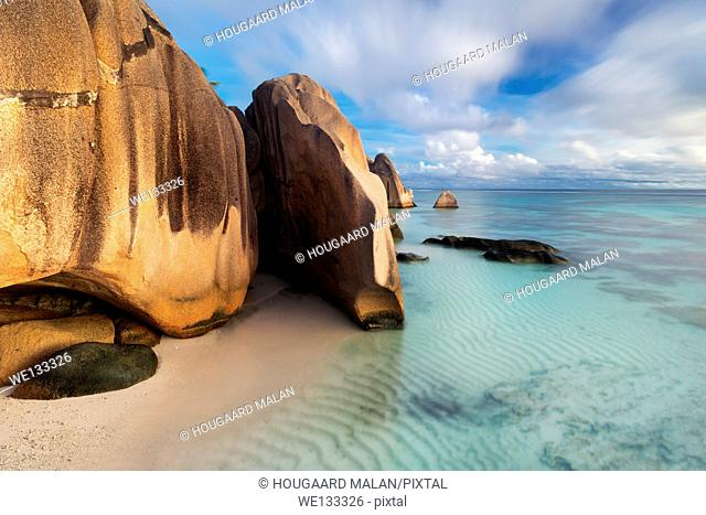 Long exposure landscape photo of a cloudy afternoon on the famous Anse source d'Argent beach. La Digue Island, Seychelles