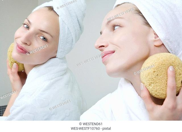 Young woman cleaning her face with a sponge