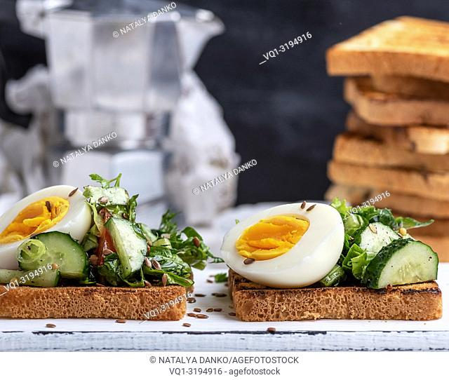 toasted square pieces of bread from white wheat flour with boiled egg, cucumber and green spinach leaves , close up