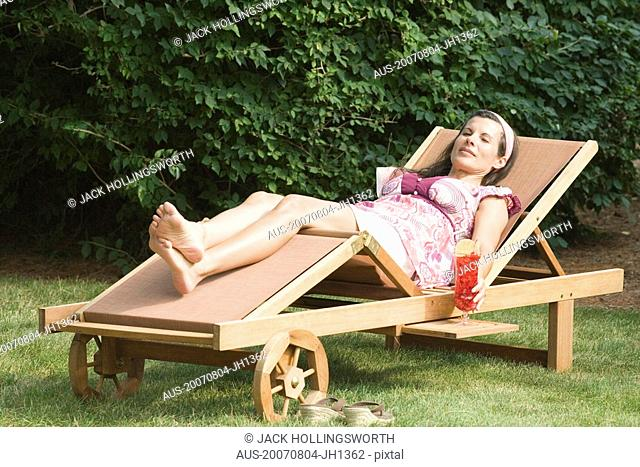 Mature woman lying on a chaise lounge