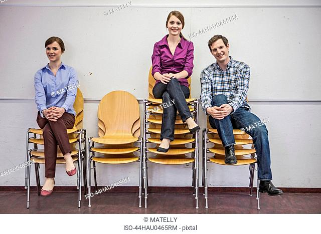 Business people on stacked chairs