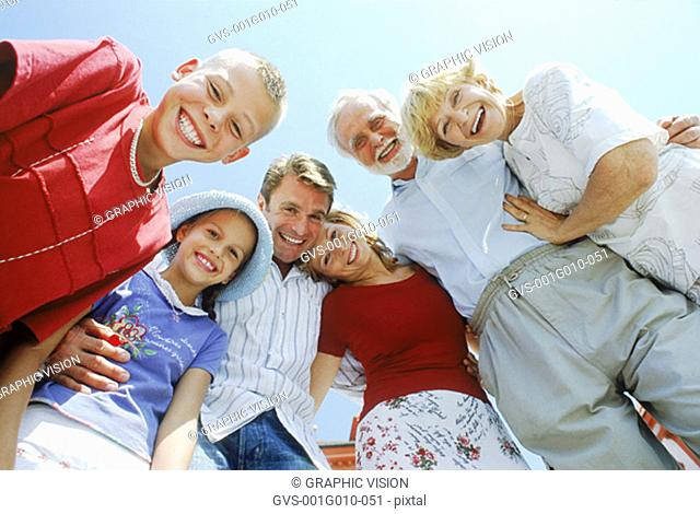 Low angle view of a family smiling and looking down