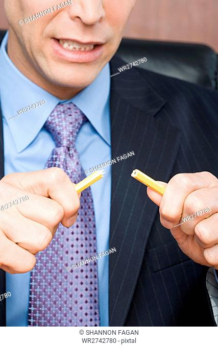 Businessman breaking pencil