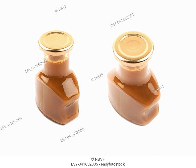 Bottle of caramel sauce isolated over the white background, set of two different foreshortenings