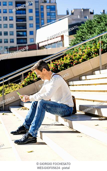 Casual businessman sitting on stairs, reading messages on his smartphone