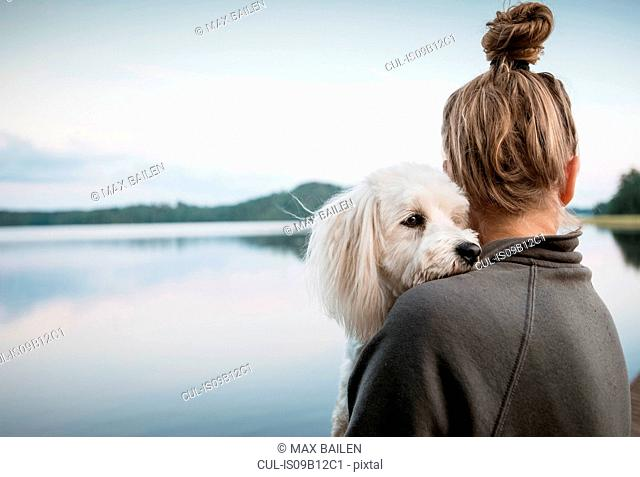 Coton de tulear dog looking over woman's shoulder at lake, Orivesi, Finland