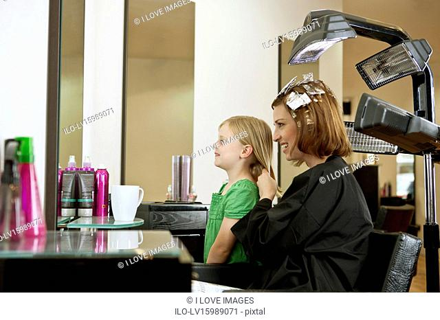 Mother and daughter looking in the mirror in a hairdressing salon