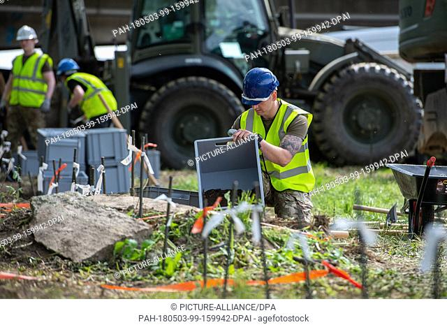 03 May 2018, Germany, Paderborn: A soldier of the British military police carries a box full of soil, which was dug out next to the river Alme