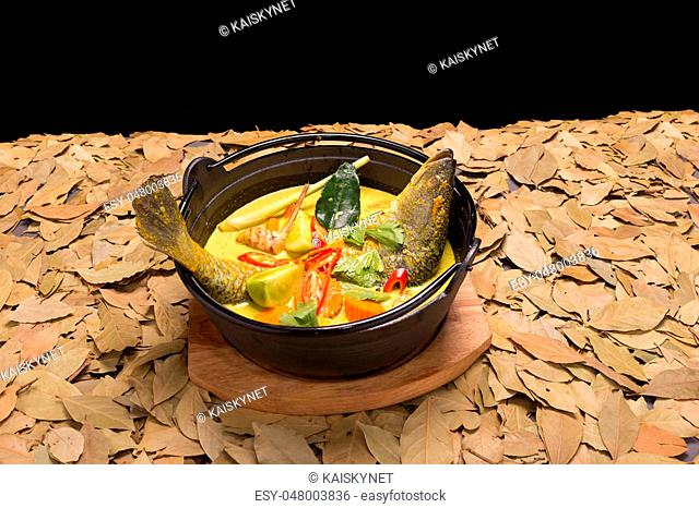 white snapper fish curry soup with tomato, red chilli, and lime leaf, black background