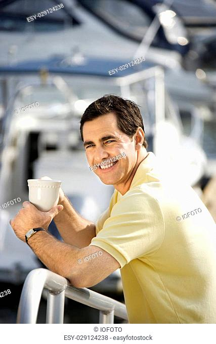 Portrait of Caucasian mid-adult male holding coffee cup at harbor looking at camera