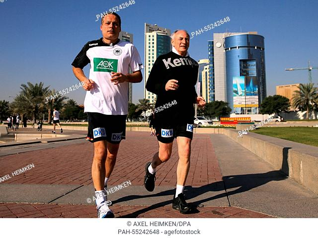The president of the German Handball Federation, Bernhard Bauer (r) and team coordinator Volker Schurr are jogging along the skyline of Doha during the men's...