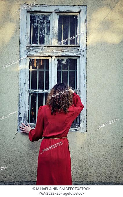 Woman standing outside the house looking through window