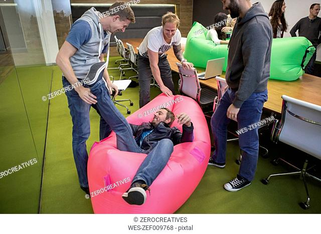 Group of business people playing around with inflatable sofas
