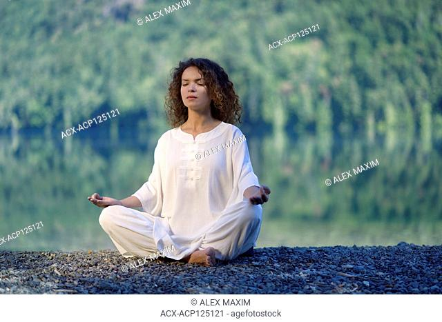 Young woman in white silk outfit meditating in the morning sunrise by the lake in the nature