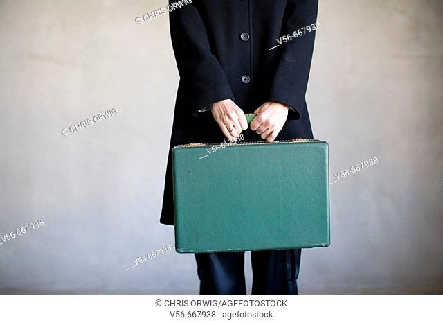 A woman's torso holding an old suitcase