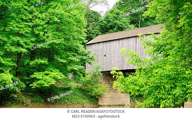 Trees surround an old wooden covered bridge, Pennsylvania, USA