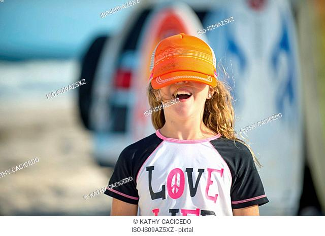 Portrait of young girl at beach, cap covering eyes