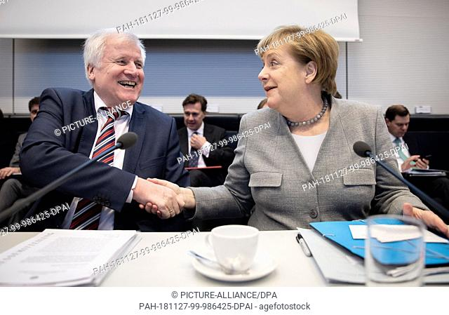 27 November 2018, Berlin: Horst Seehofer (CSU), Federal Minister of the Interior, Building and Home Affairs, and Chancellor Angela Merkel (CDU) participate in...