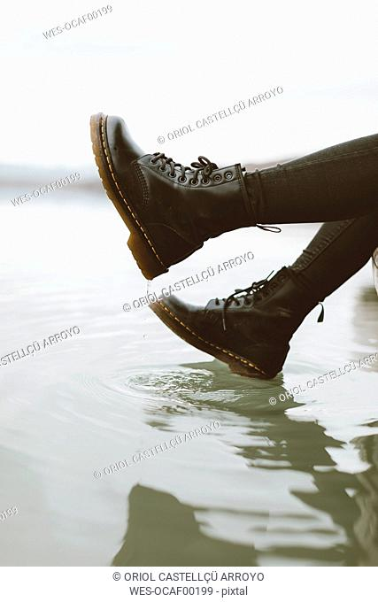 Woman wearing black boots touching water surface of lake, partial view