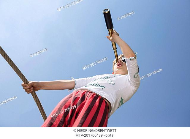 Boy standing on pirate ship in playground and looking through telescope, Bavaria, Germany