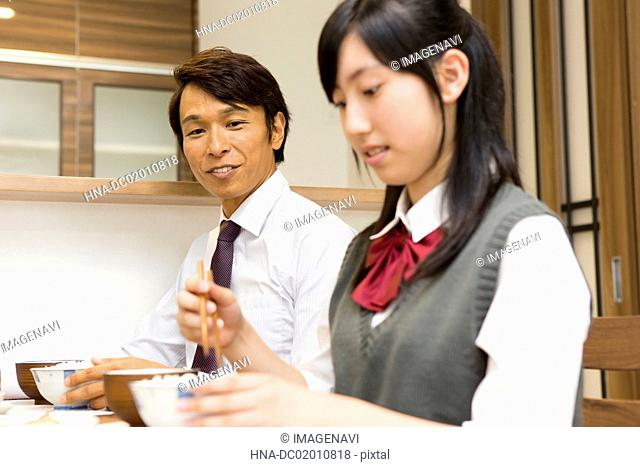 A father and daughter at a dining table